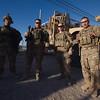 Troops, preparing to return to their Forward Operating Base, pose beside their vehicle.