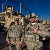 Two officers pose in front of their vehicle prior to leaving the Kandahar base.