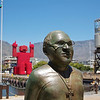 Statue of Desmond Tutu with world cup fan made out of Coke bottle carriers in background.