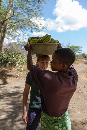 Driving into Arusha from the farm, we saw a woman walking by the road balancing a heavy load of bananas bound for the market. We stopped and she showed us how she balanced the load, and we tried to copy her style with mixed success. Here Suzy gets to try it out