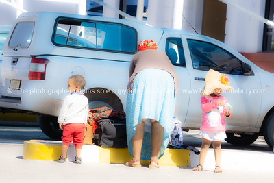 Woman facing away and bending over her baggage with two small children waiting to be collected.