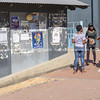 Group three African young women standing street conversing in front grungy wall of peeling posters.