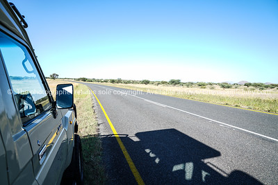 Safari vehicle parked by sealed road with shadow.