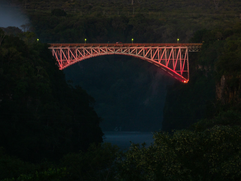 The bridge is lit up at night, casting a red glow as an accent to the dark river below.