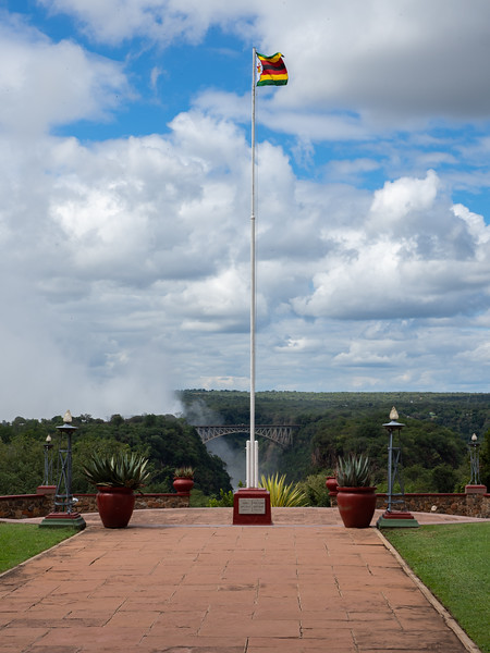 A view of the bridge over the Zambezi River from the terrace of the Victoria Falls Hotel, with the flag of Zimbabwe blowing in the wind.