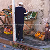 """Trying to make a buck, little boy stands by wall as father sets up fruit stall in the Malay section of Cape Town.<br /> Model released; no, for editorial & personal use. SEE ALSO:  <a href=""""http://www.blurb.com/b/685976-africa"""">http://www.blurb.com/b/685976-africa</a>"""