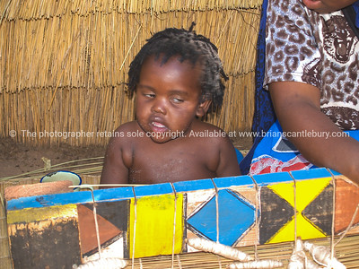 African Child sits watching the tourists file by. Model released; no, for editorial & personal use. SEE ALSO: www.blurb.com/b/685976-africa