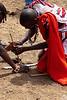 making fire by rubbing sticks, maasai village