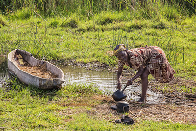 Okavango Delta, Botswana A local woman who accompanied us as a makoro canoe poler cleans a pan in preparation for cooking locally caught fish.