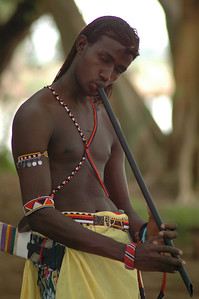A young Samburu man at Larson's Camp in the reserve has a critical job: armed with a slingshot he must shoo the monkeys away from the dinner table!  In quieter moments, his music entertains us.