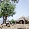 Melese Amade sidder i skuggen under et træ uden for familiens hytte