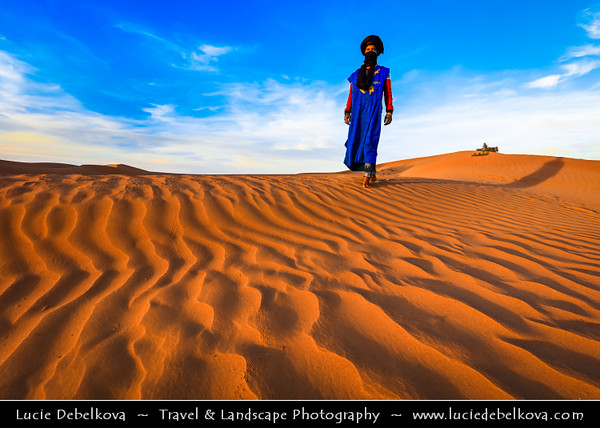 Northern Africa - Kingdom of Morocco - Sahara Desert - Zagora Province - M'Hamid El Ghizlane - Erg Lehoudi - Er Lihoudi - Classic desert landscape with constantly changing sand dunes, lines and shapes - Large sea of dunes formed by wind-blown sand - Local Bedouin in traditional blue dress