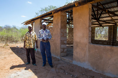 Chief of the village and teacher in front of new school that's is  waiting to be finished.