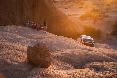 Spitzkoppe, Namibia After driving their 4-wheel drive truck up the granite rocks, campers sit and enjoy a beer as the sun sets over Spitzkoppe.