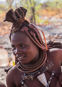Northern Namibia A Himba woman smiles as she barters with customers while selling her handmade jewelry.
