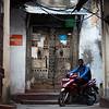 A local man rides his motorbike through the alleys of Stone Town in Zanzibar, Tanzania.