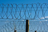 Coils of barbed wire on top of a fence provide security at a penitentiary in South Africa. The barb wire is symbolic of protection and security -- but also of the freedom that lies beyond the perimeter of the prison walls.