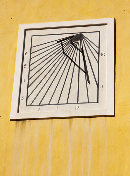 An old-fashioned sun dial on a stained yellow wall on the kat, or command building, in the Castle of Good Hope in Capetown, South Africa. As marked, using the shadow lines, it keeps time from 10am to 6pm.