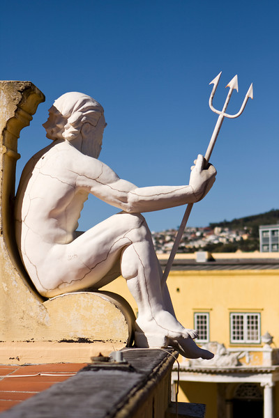 A statue of Neptune holding a trident that is looking over a courtyard on the roof of the Castle of Good Hope in Cape Town, South Africa. Looking closely, a series of cracks are visible throughout sculpture.