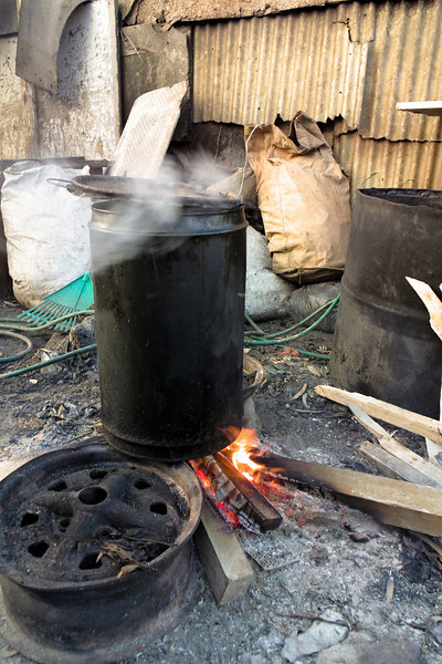 A pot of sheep's head soup being cooked over an open fire in a township near Cape Town, South Africa. In the background, corrugated tin sheets cover the walls of the shacks surrounding the cooking area.