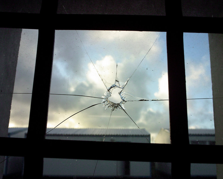 A broken window, with cracks radiating from the shattered hole in the center, in a high school in a South Africa township near Cape Town symbolizes a future life with little or no hope.
