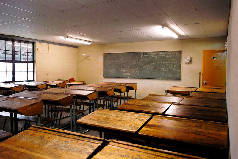 The interior of a classroom in a South African township. The blackboard has the current material for the class. The wooden desks are covered with graffiti.