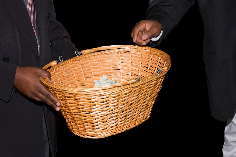 A basket being passed around at a Methodist Church in a South African township to collect donations.