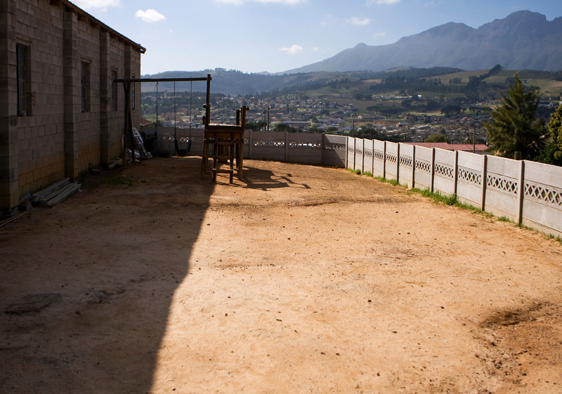 An empty playground for a preschool and church in Kayamandi township in South Africa. With just a swing set and the bare ground, it is fairly typical.