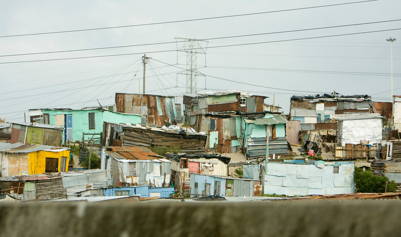 A view of an informal settlement or township near Cape Town, South Africa. The small homes are built of scraps of tin and plywood to provide shelter.