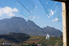 The mountains near the city of Stellenbosch, South Africa as seen through a broken glass window in the informatl settlement of Kayamundi.