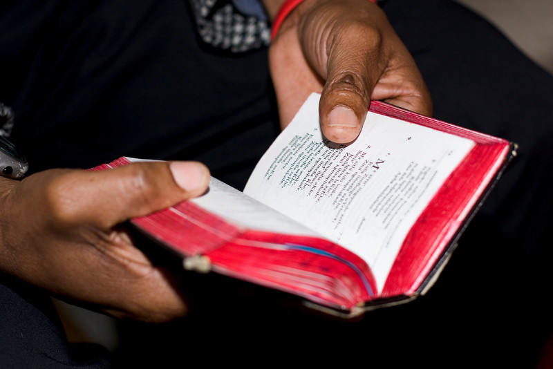 Two hands holding an old, well-used prayer book at a Methodist church service on Sunday are symbolic of faith of South African people. Note: shallow depth of field is focused on just the thumb and the nearby text.