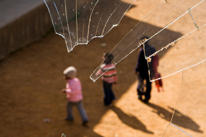 A group of three schoolchildren viewed through the remnants of a broken window at a pre-school in a township in South Africa. The sharp shards of broken glass are symbolic for a culture where there is hope but still great difficulty in enabling pesonal achievement.