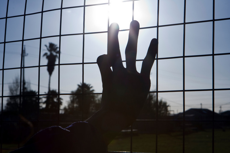 Reaching for the sun in a South African township, a child's hand grasps the wires on a fence as if stretching for freedom. The sunburst is located at the tip of the middle finger.
