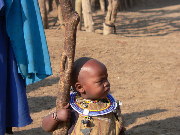 A young Masai girl watching the men of the tribe do their jumping competition.