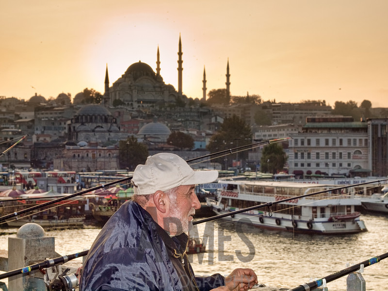 Fishing from the Galata Bridge with the Suleymaniye Mosque in the background, Istanbul, Turkey