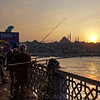 Fishing from the Galata Bridge at dusk with the Suleymaniye Mosque in the background, Istanbul, Turkey