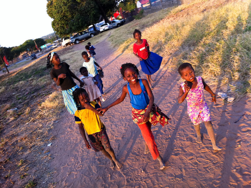 "<span id=""title"">Chasing White People</span> We arrived back home as school was getting out. We seemed to be such a novelty to the kids, they literally ran after us. This shot is a little blurry and taken with my phone, but I love all the different expressions."