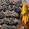 "<span id=""title"">Charcoal</span> I remember running ahead so I could photograph this brightly colored woman as she walked in front of the charcoal bundles for sale. What a contrast."