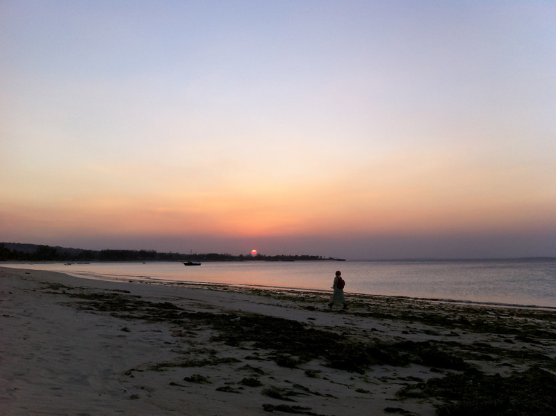 "<span id=""title"">Hazy Sunset</span> A local woman walking along the shore at sunset. The sun turned a brilliant red color, probably because of smoke. There was always something on fire..."
