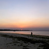 """<span id=""""title"""">Hazy Sunset</span> A local woman walking along the shore at sunset. The sun turned a brilliant red color, probably because of smoke. There was always something on fire..."""