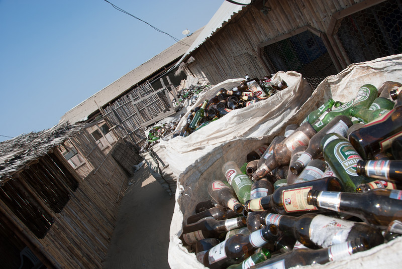 "<span id=""title"">Glass Bottles</span> These bottles are pretty much the only sign that the surrounding buildings/shacks are bars at night."