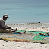 "<span id=""title"">Net Repair</span> A man repairing a very large net on the beach. Later we saw four people carrying the net around the shallow water. I couldn't tell how much they caught."