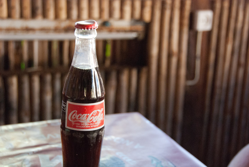 """<span id=""""title"""">Coca-Cola</span> I found it interesting that when you get a soda in Pemba, you're only buying the liquid. The shop or restaurant owner takes the bottle back and exchanges them for filled bottles. Everything is glass, and every bottle we got had obviously been used before."""