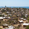 """<span id=""""title"""">Scenic Neighborhood</span> Here's the amazing view (minus my wife and I) from a spot along the main road that leads to downtown Pemba. This is pretty typical of the local houses, which are bamboo frames with mud/clay plaster applied."""