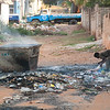 "<span id=""title"">Trash Management</span> Just a block from the main intersection of town, this person was going through the trash as it burned around them."