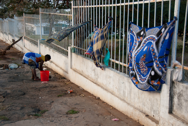 """<span id=""""title"""">Washing Clothes</span> This woman was washing clothes on the sidewalk across from Pemba's hospital - the main hospital for the whole province.  The sidewalks in general were very damaged, with lots of cracks and broken concrete, as well as large holes that you'd never see in the US without a barrier around it."""