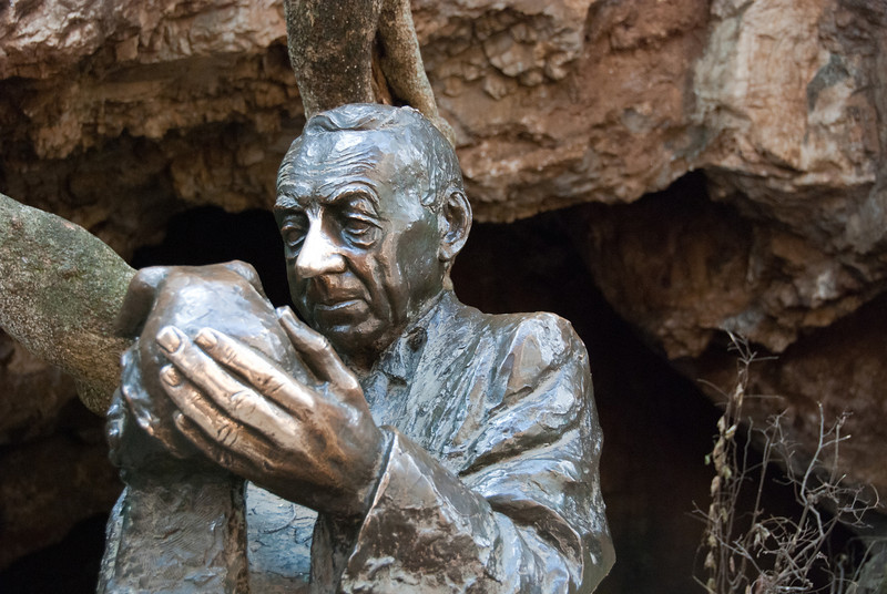 """<span id=""""title"""">Dr. Robert Broom</span> <em>Sterkfontein Cave, Cradle of Humanity</em> This is a statue of the archaeologist who first discovered our hominid ancestors in the cave that you can see behind him. Why the shininess? Well, you can rub his nose for good luck, or his hand for wisdom. You can't rub both though, or you'll die. It's totally true."""