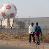 "<span id=""title"">Passing By</span> <em>Soweto</em> Across from the Buy & Braai, these two gentlemen walked by each other as a massive ABSA balloon looms in the distance. ABSA is a local bank, and the giant balloon was part of a mall and you can ride in it."