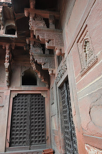 Wooden doors and decorated columns at Agra Fort (Lal Qila).  It is about 2.5 km northwest of the Taj Mahal. The fort can be more accurately described as a walled palatial city.
