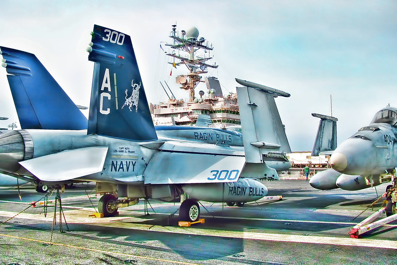 Strike Fighter Squadron (VFA) 37 Ragin' Bulls 300 on Flight Deck of USS HST (CVN 75) with View of Aircraft Carrier USS Abraham Lincoln (CVN 72) Island and Bridge in Background.
